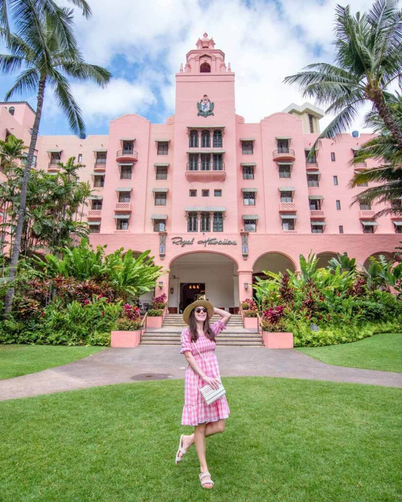 Woman in pink dress walking in front of the Royal Hawaiian hotel