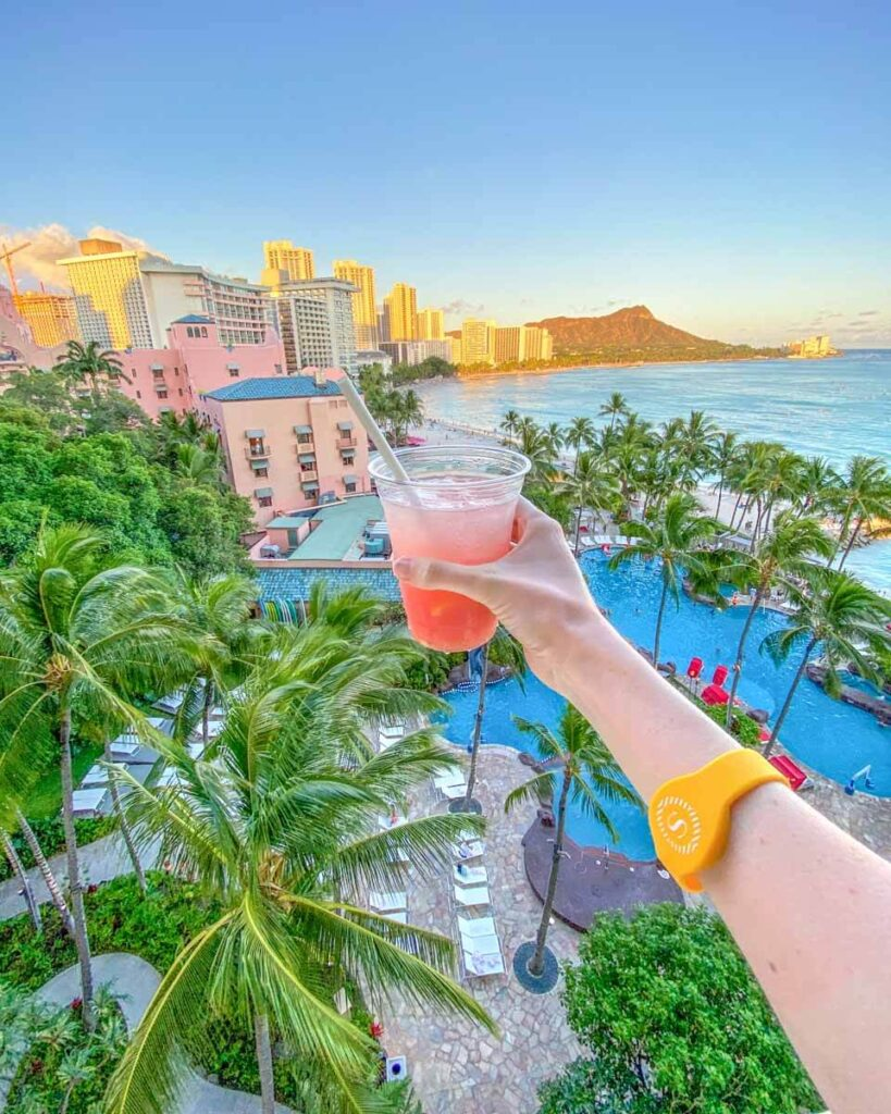 Woman holding out cocktail over a view of the Sheraton Waikiki