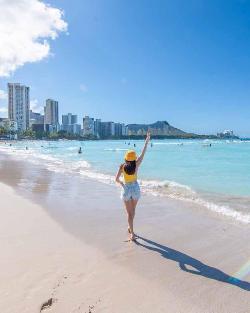 Woman walking along Waikiki Beach with Diamond Head in the distance