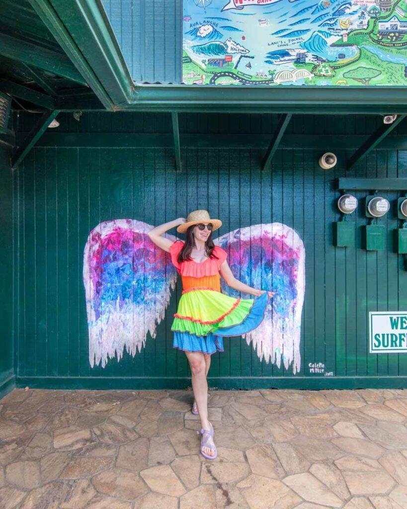 Woman in front of Colette Miller angel wings mural in Haleiwa