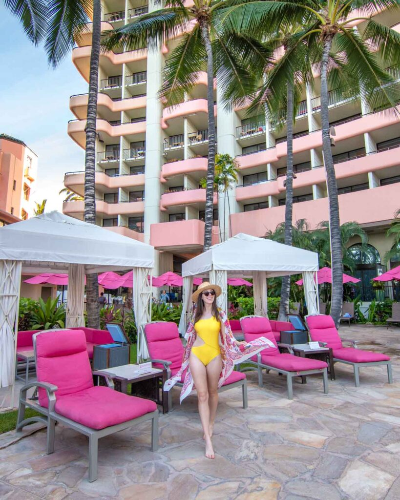 Woman in yellow bathing suit in front of pink pool chairs at the Royal Hawaiian Hotel in Honolulu