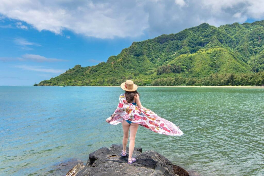 Woman standing on rock next to water in front of green mountain in Hawaii