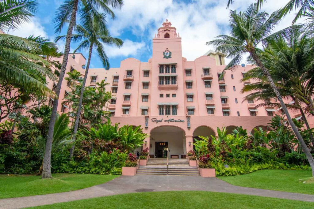 Façade of the Royal Hawaiian Hotel with gardens surrounding it.