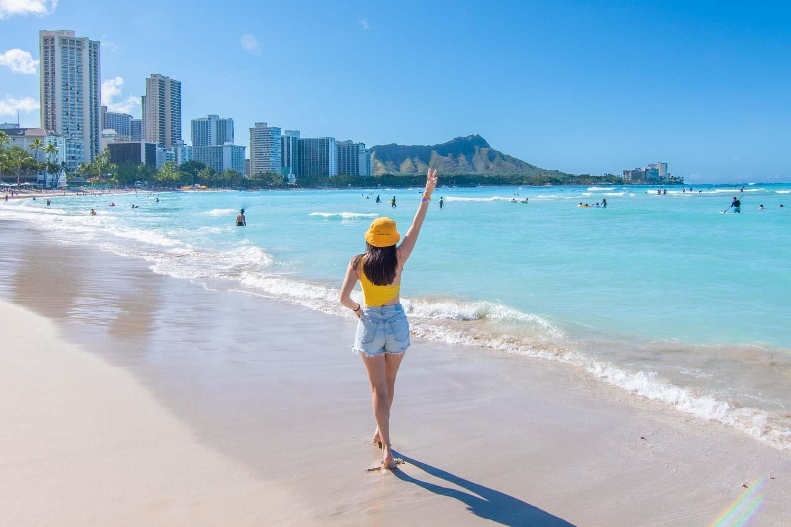 Woman walking down Waikiki Beach with hand making a peace sign