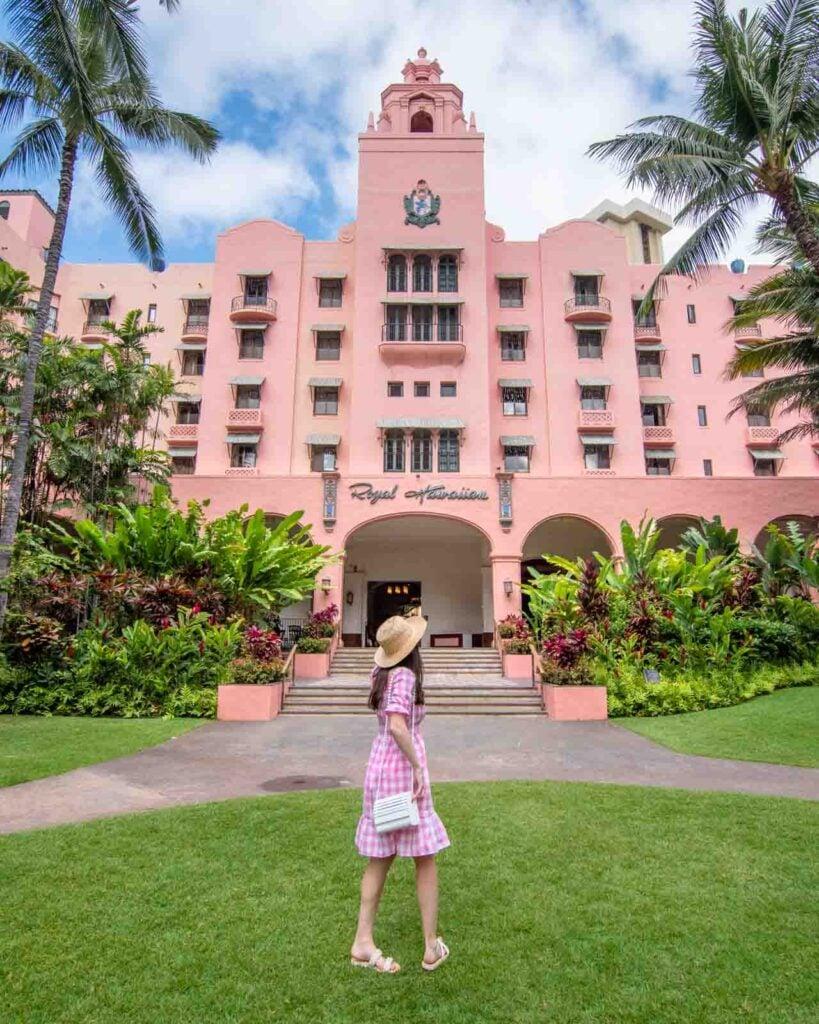 Woman in pink dress walking in front of the Royal Hawaiian Hotel in Honolulul