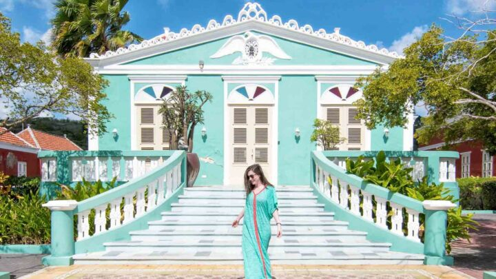 woman walking in front of colorful house in curacao