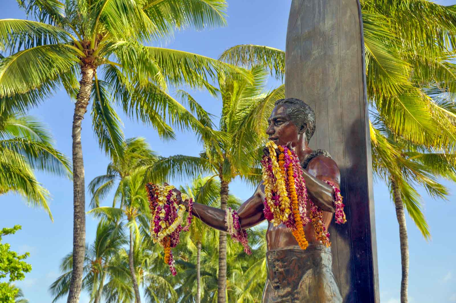 The bronze statue of Duke Kahanamoku on Kuhio Beach, with leis draped over the arms and palm trees surrounding it.