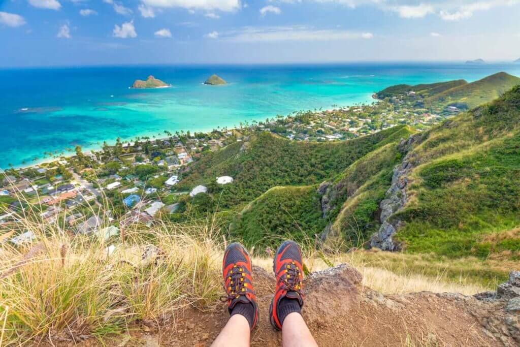 The view from the Lanikai Pillbox hike, showing a person's hiking boots on the hill and the ocean in the distance