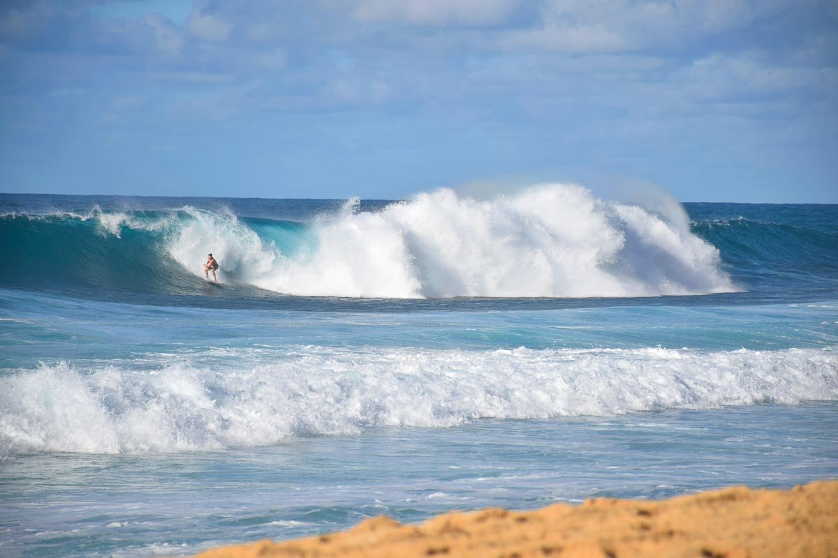 Surfer catching a wave at the famous Banzai Pipeline on the North Shore of Oahu.