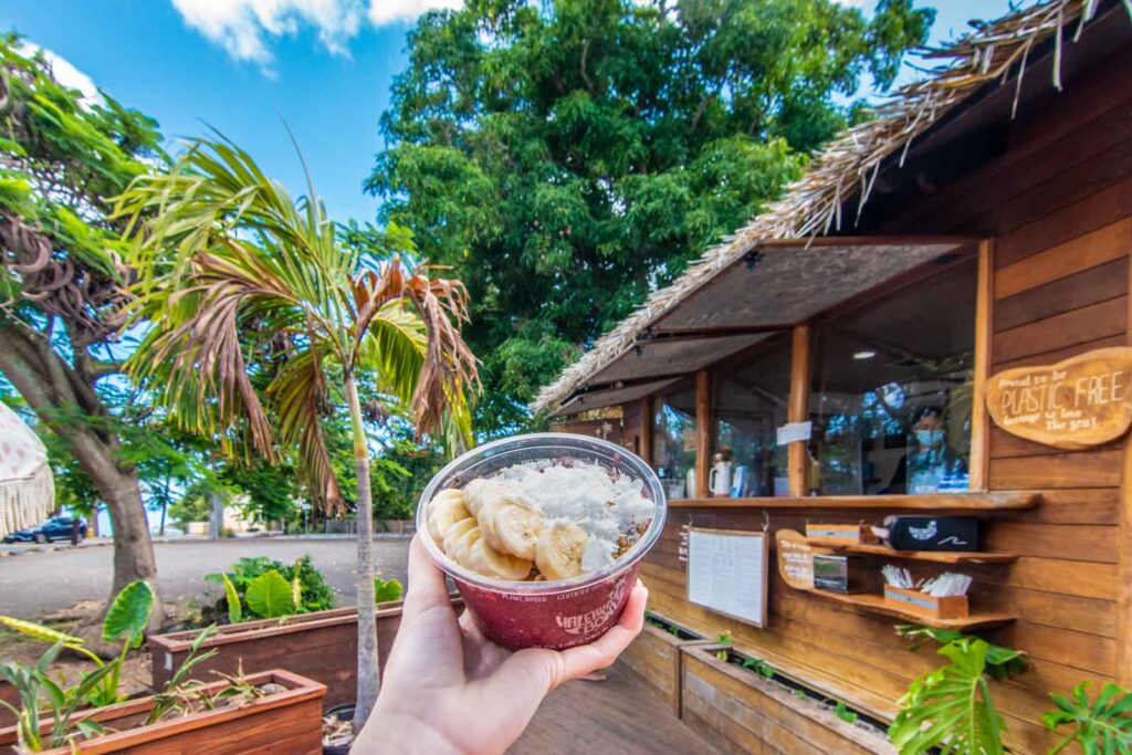 Açai bowl with coconut shavings and bananas in front of Haleiwa Bowls kiosk in Haleiwa Town, Oahu.