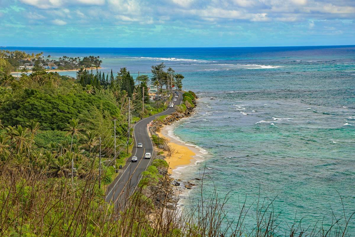 Bird's eye view of cars driving down Kamehameha Highway as the road winds along Oahu's coast.