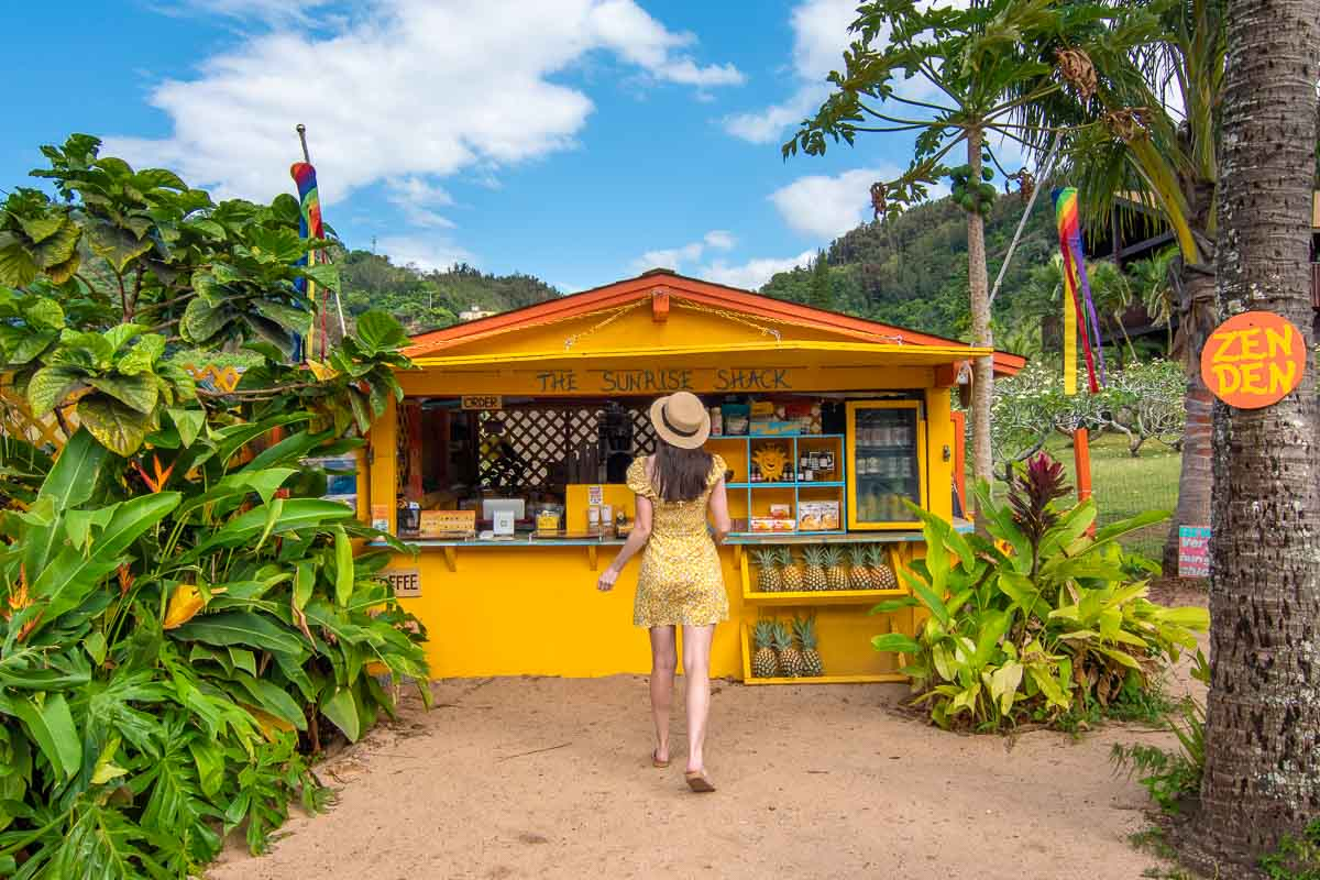 Woman in yellow dress walking in front of the yellow Sunrise Shack restaurant across from Sunset Beach on Oahu's North Shore.