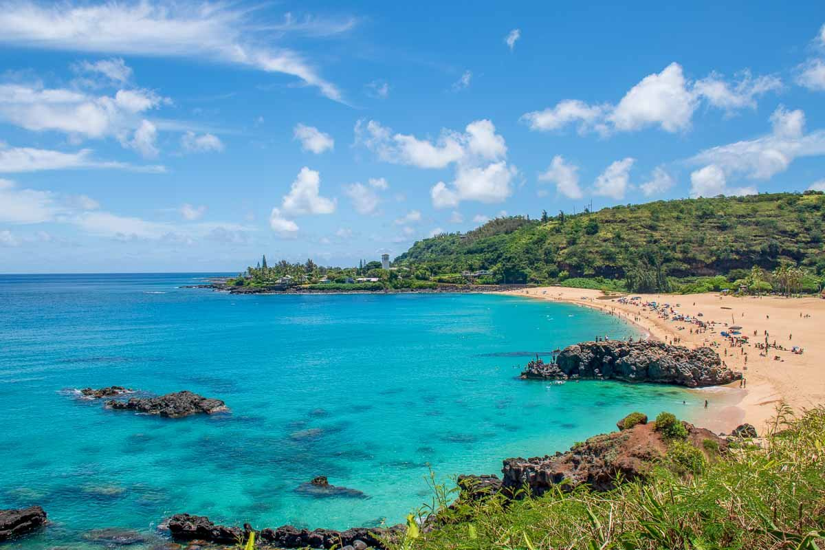 View of Waimea Bay Beach Park, showing clear water and rock formations.