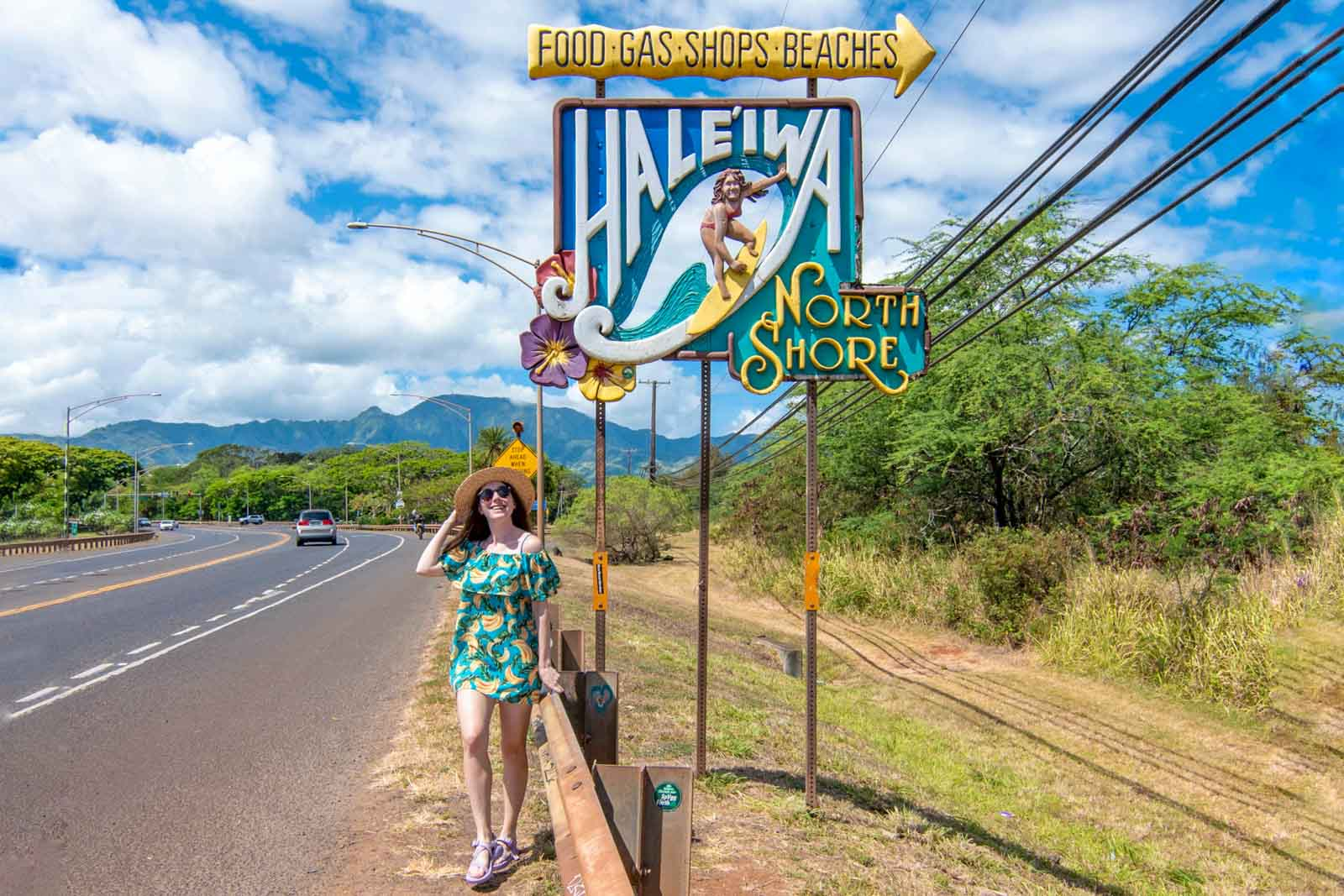 Woman posing for a picture in front of the Haleiwa surfer sign in Haleiwa Town, Oahu.