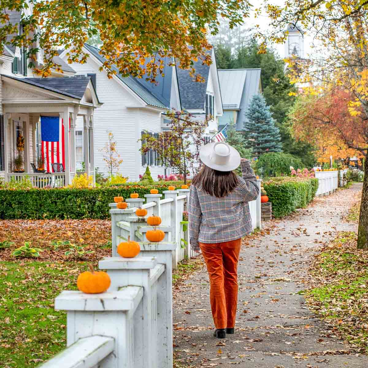Woman walking down street in Woodstock, Vermont that is decorated with pumpkins for Halloween